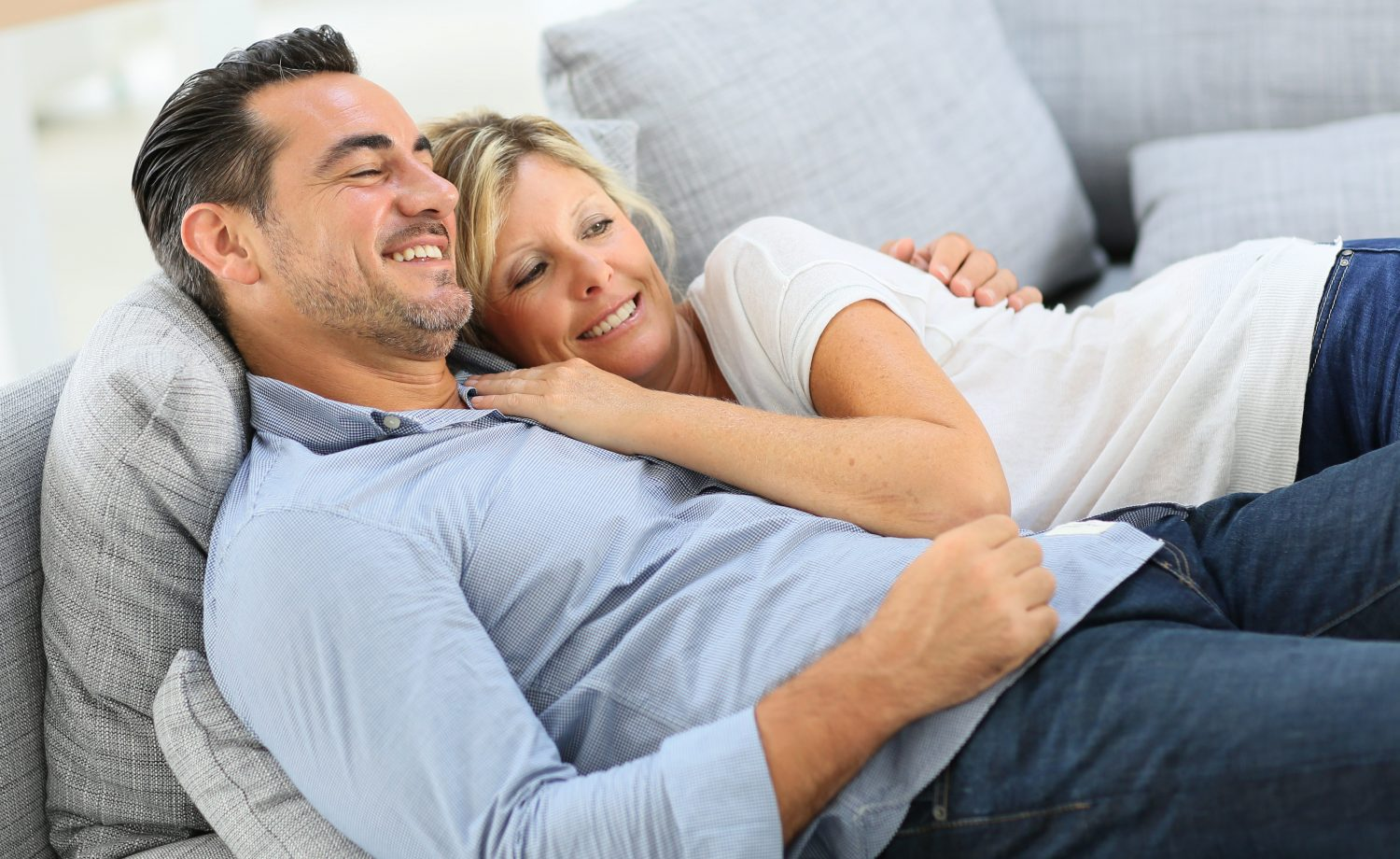 Middle Aged Couple In Sofa Watching Tv